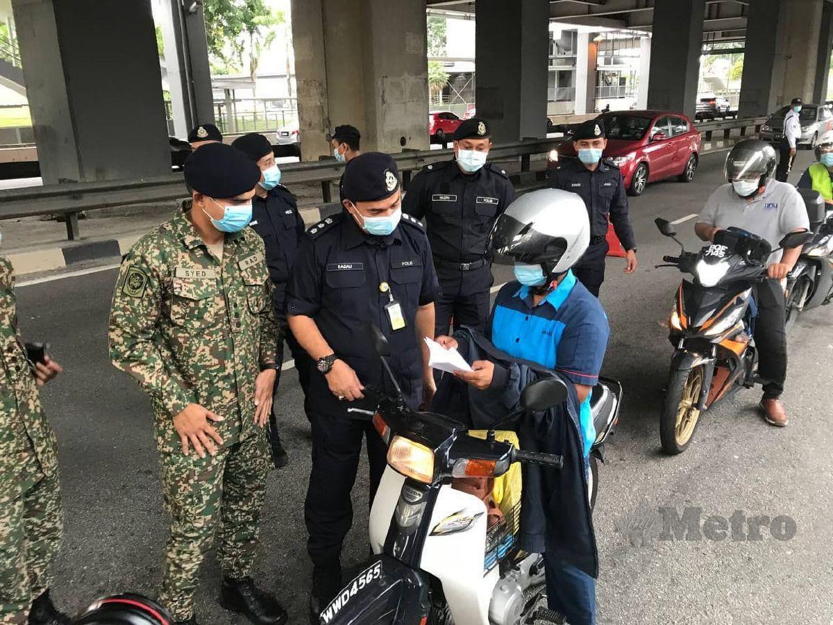 ASISTEN Komisioner Razali Abu Samah melakukan pemeriksaan terhadap pemandu kenderaan yang melalui SJR di Lebuhraya Bukit Jalil berhampiran Stesen Transit Aliran Ringan (LRT) Bandar Kinrara 5, Serdang, hari ini.