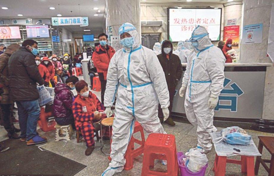 KAKITANGAN perubatan memeriksa pesakit  di hospital di Wuhan.