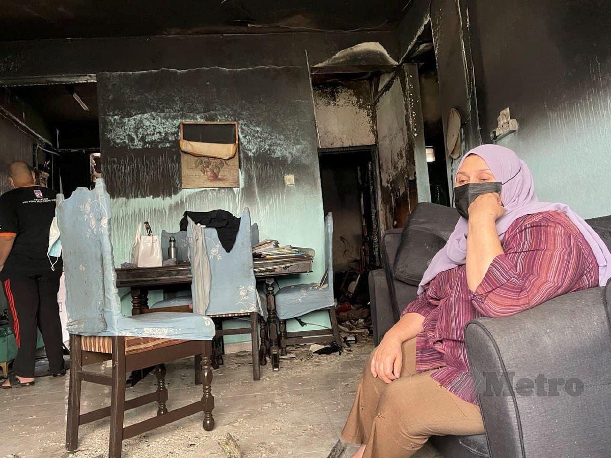 CHE Raima termenung di ruang tamu rumahnya yang musnah di jilat api di Flat Sri Kolam. FOTO Ahmad Rabiul Zulkifli
