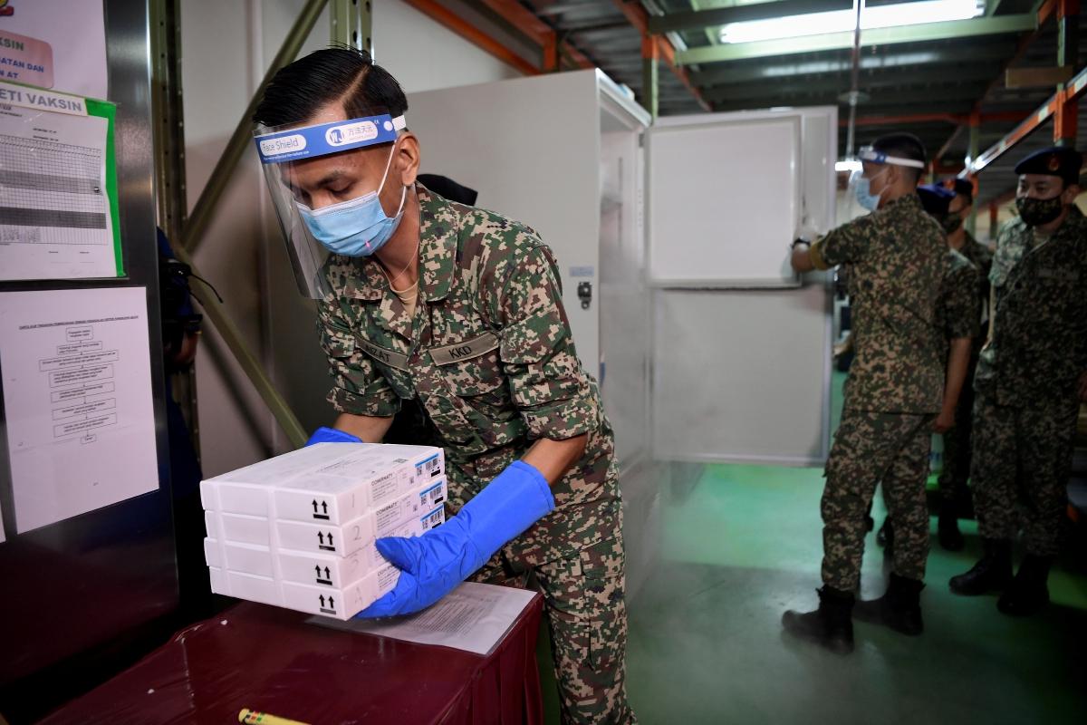 ATM membawa keluar vaksin COVID-19 jenis Pfizer-BioNTech dari kotak penghantaran khas.