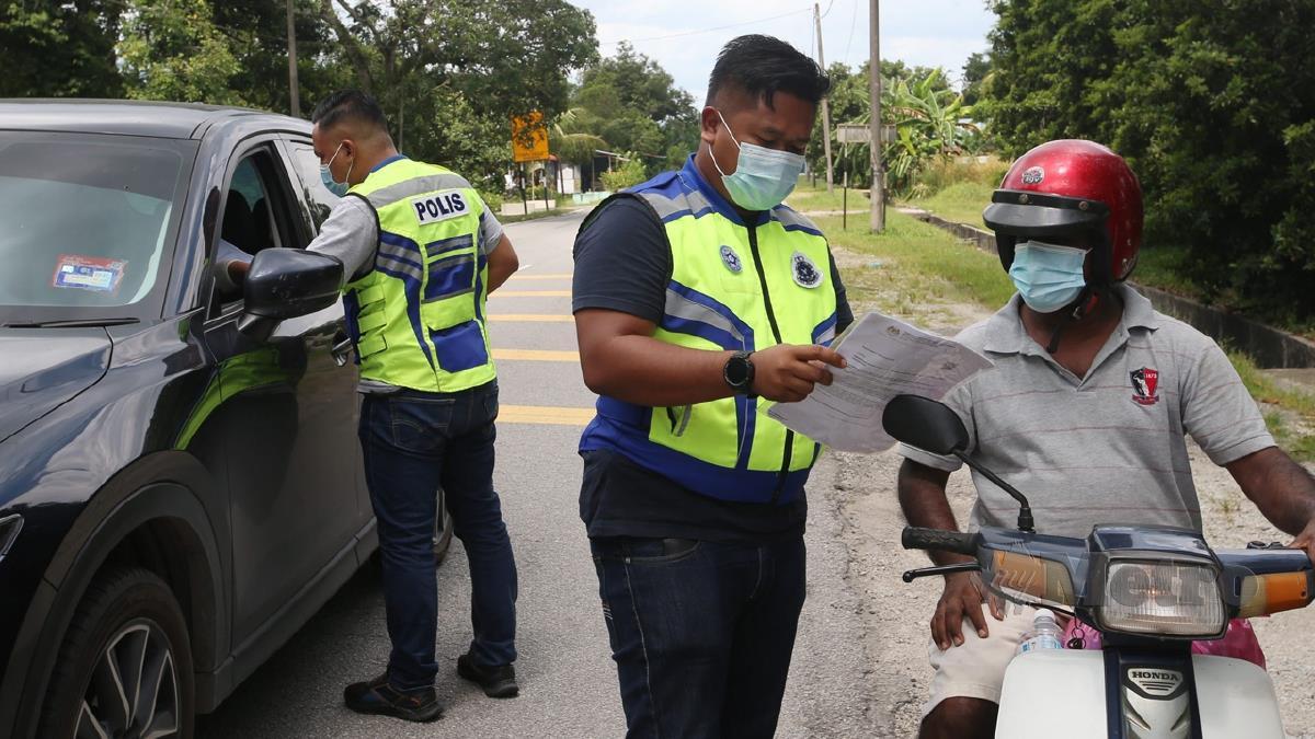ANGGOTA polis melakukan pemeriksaan pada SJR bergerak ketika menjalankan pemantauan pematuhan dan penguatkuasaan SOP Perintah Kawalan Pergerakan. FOTO Danial Saad