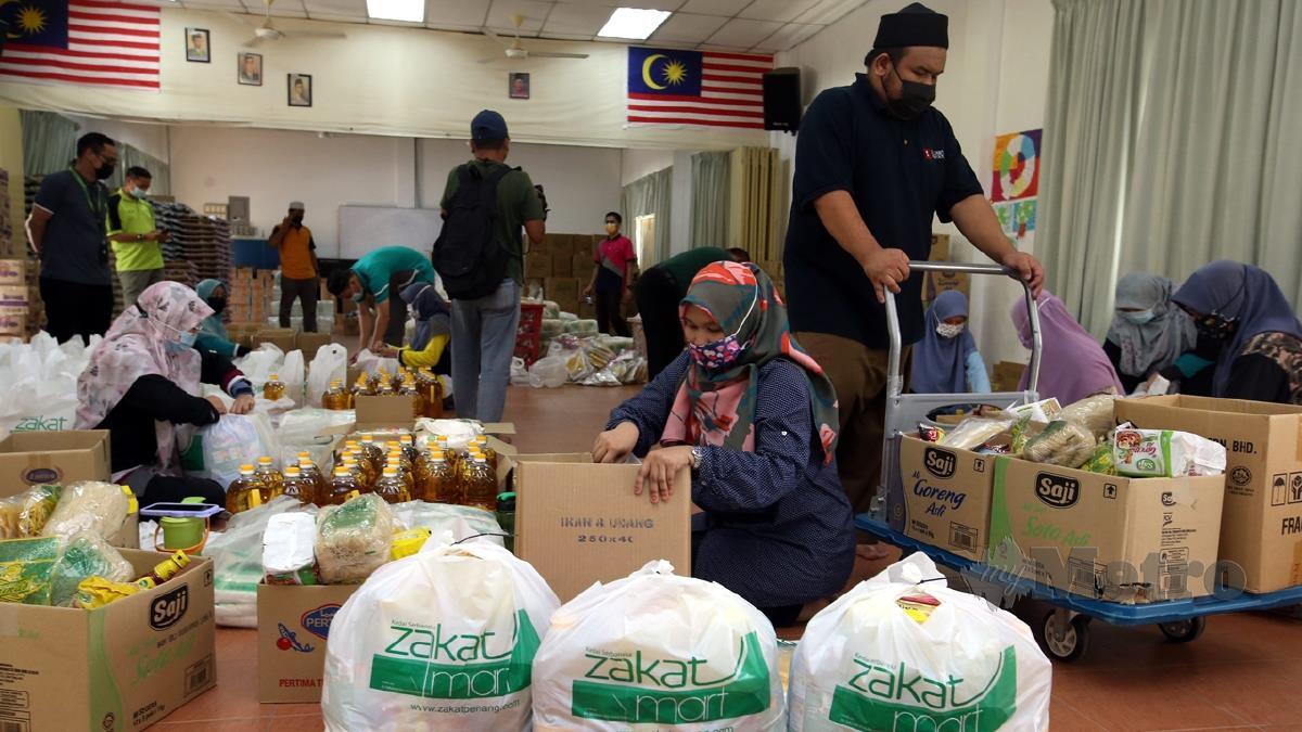 KAKITANGAN Zakat Pulau Pinang membungkus belakan makanan untuk program Skim Bantuan Makanan Kecemasan ZPP di Inapan Kasih Sayang ZPP. FOTO Danial Saad