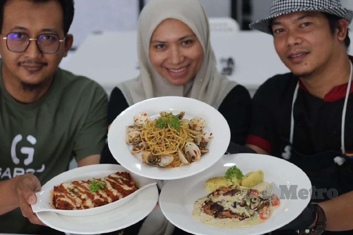 TUAN Mohd Affendi (kanan) bersama adiknya, Tuan Zuraihan (tengah) dan adik ipar, Marzukey Mohd Yusoff menunjukkan menu pilihan utama pelanggan di restoran mereka di Lembah Sireh, Kota Bharu.