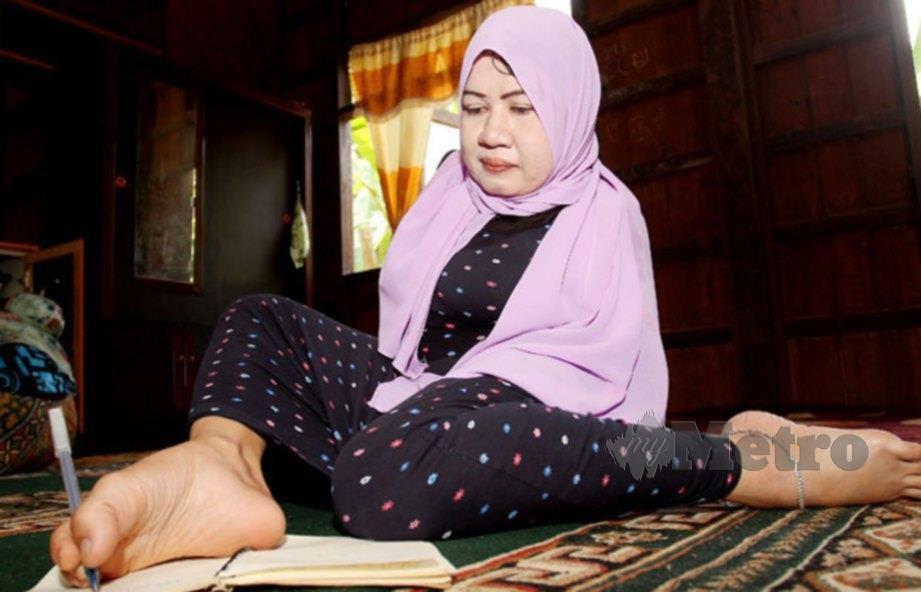 LAILA yang tidak memiliki sepasang tangan sehingga paras bahu tidak kekok menulis dengan menggunakan kaki ketika ditemui di rumahnya di Kampung Sungai Pas. FOTO Nik Abdullah Nik Omar