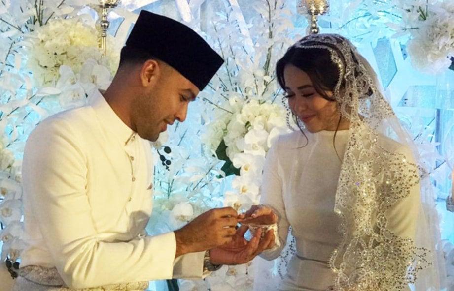 SHAZLI Azhar sedang menyarung cincin di jari manis Emma Maembong. FOTO Ihsan Zaidi Mohd