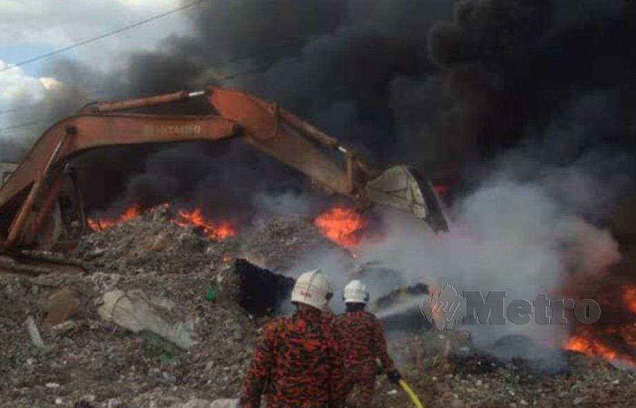 ANGGOTA bomba sedang melakukan kerja pemadaman kebakaran di tapak pelupusan sampah di Semeling, Bedong.