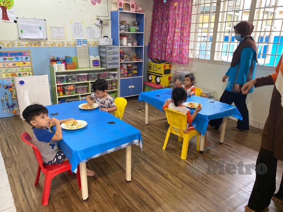 PENGASUH Taska Halaman Ilmu memastikan kanak-kanak menjaga jarak sosial ketika waktu makan. FOTO Murnaena Muhammad Nasir