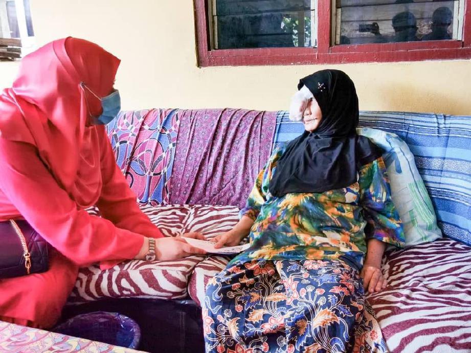 DATUK Seri Rina (kiri) melawat Che Mariam Idris (kanan) ketika mengadakan lawatan di rumahnya di Kampung Baru Pantai Mek Mas, di Kota Bharu, di sini, semalam. FOTO ihsan Keluarga