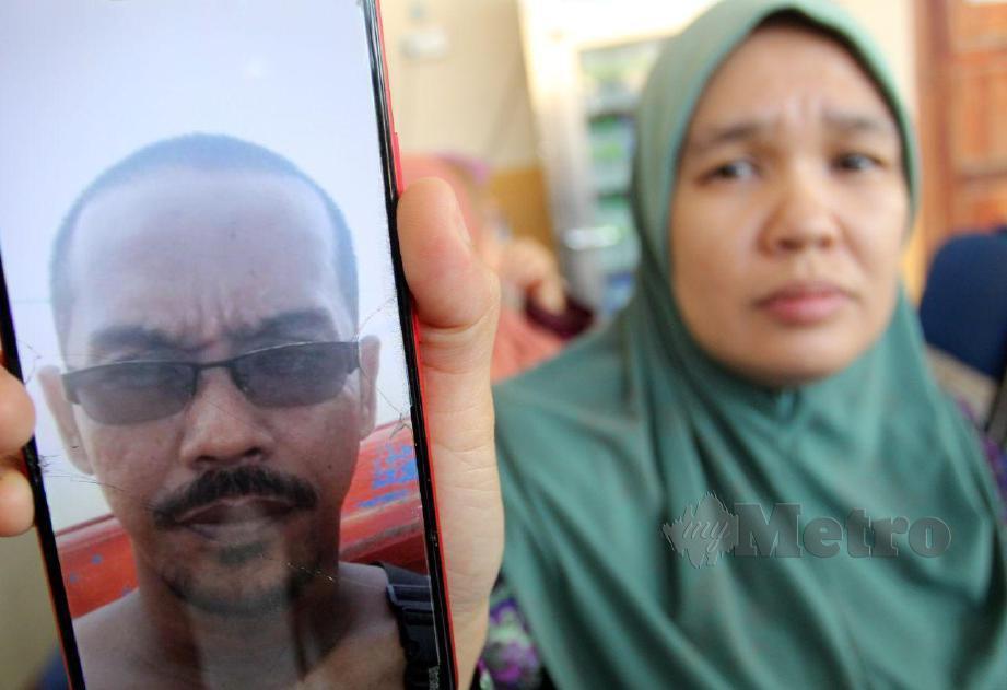 ROSMALIZA menunjukkan gambar suaminya Mohd Syafizam Daud, 43 yang maut selepas bot yang dinaikinya terbalik dalam kejadian di perairan Bachok ketika ditemui di Unit Forensik Hospital Raja Perempuan Zainab II (HRPZ II). FOTO Nik Abdullah Nik Omar