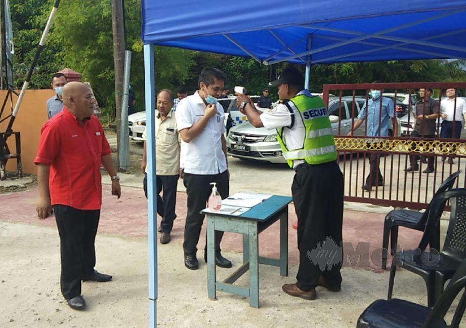DR Mohd Radzi Jidin, (dua kanan) turut sama memeriksa suhu sebelum melawat lokasi guru maut akibat jatuh dari balkoni di SK Batu Gajah, di sini, hari ini. FOTO Syaherah Mustafa