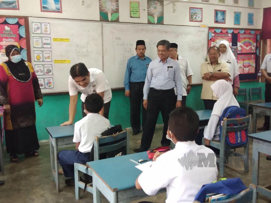 DR Mohd Radzi Jidin, sempat beramah mesra dengan salah seorang murid di SK Batu Gajah, di sini, hari ini. FOTO Syaherah Mustafa