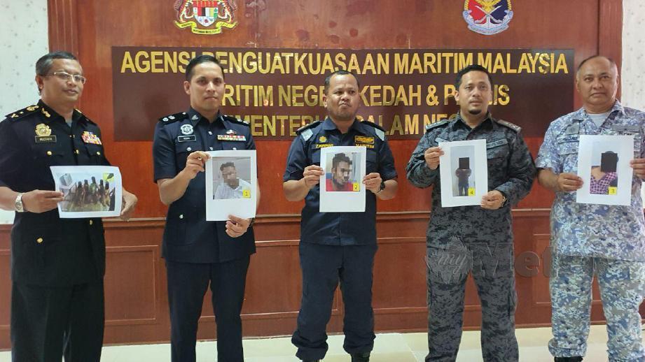 ZAWAWI (tengah) diiringi Mustafa (kiri sekali), Iqbal (dua dari kiri), Zuhair (dua dari kanan) dan Hamid (kanan sekali) menunjukkan gambar suspek yang aktif membawa masuk etnik Rohingya. FOTO Hamzah Osman