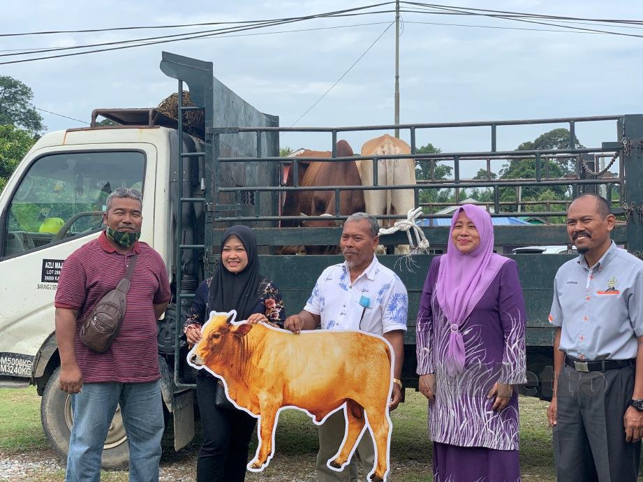 DATUK Dr Wan Norashikin Wan Noordin (dua kanan) menyerahkan dua daripada lima lembu korban untuk Dewan Undangan Negeri (Dun) Kampung Gajah. FOTO Noor Hidayah Tanzizi