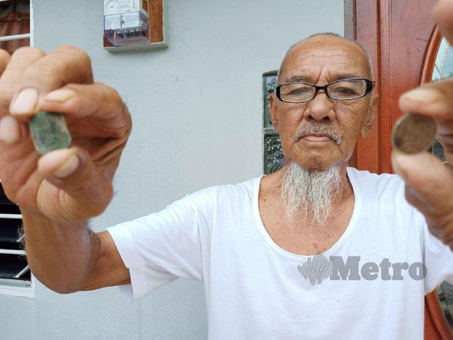 RAMLI menunjukkan duit syiling 1 sen dan 10 sen British yang masih disimpan di rumahnya di Batu Hampar. FOTO Nazri Abu Bakar