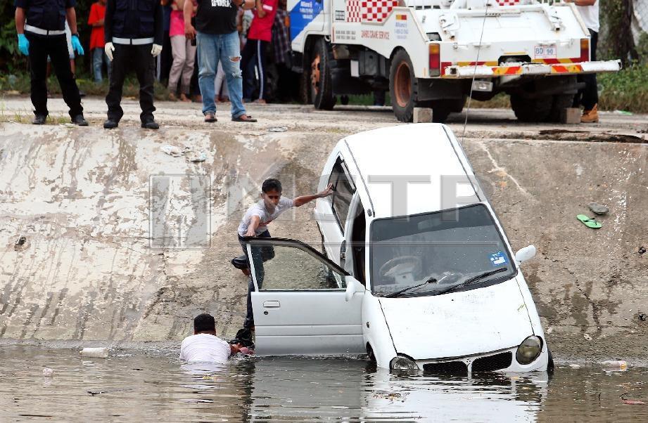 PERODUA Kancil suspek ditarik naik selepas terjunam ke dalam Sungai Sembulan. FOTO Malai Rosmah Tuah