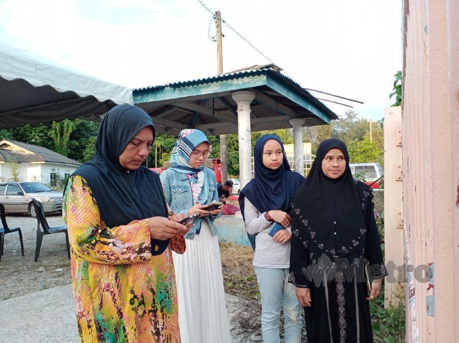 KAKAK mangsa bot terbalik, Aida Ismail, 50, (kiri) menunggu berita mengenai adiknya, Arman Ismail, 43, yang masih hilang di Jeti Perikanan Kemasin setiap hari. FOTO Nor Amalina Alias