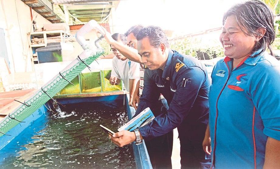 WEE (kanan) memeriksa tangki menempatkan spesies ikan larangan.