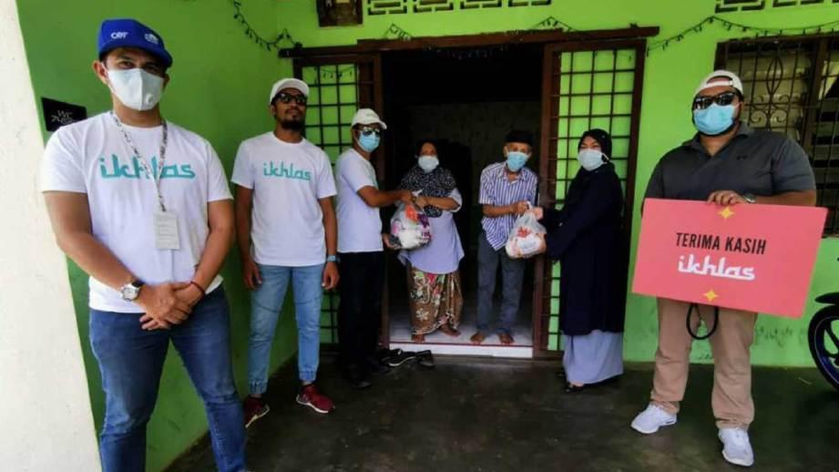 FIZZ Fairuz (kiri) dan Ketua Ikhlas, Ikhlas Kamarudin (kanan) bersama penerima sumbangan barang keperluan asas di Maran, Pahang.