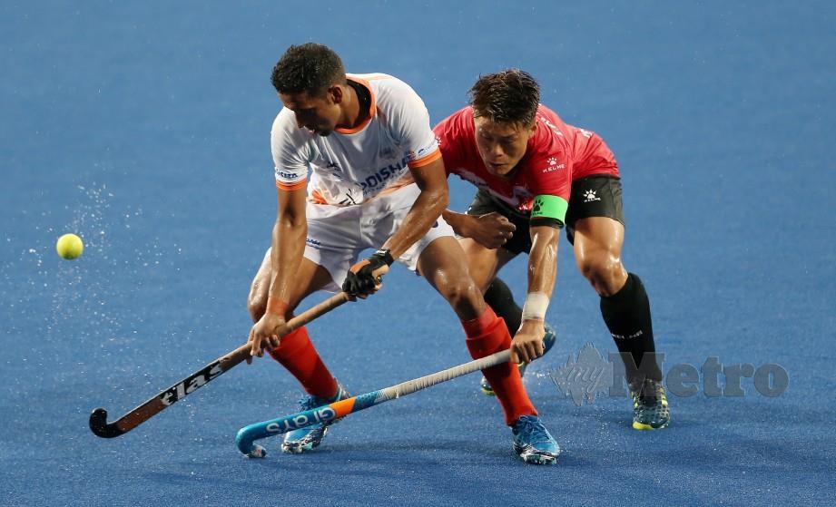 PEMAIN Korea, Lee Nam Yong (kanan) menghalang pemain India, Gurinder Singh di Stadium Azlan Shah, Ipoh, hari ini. — FOTO Effendy Rashid