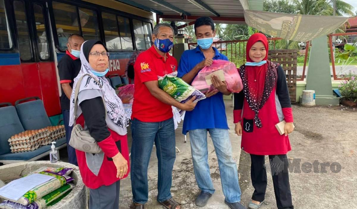 SAAD (tengah) bersama isterinya, Robiah menyampaikan sumbangan barangan keperluan di Infaq Mall Masjid Permatang Rambai. FOTO Nur Izzati Mohamad