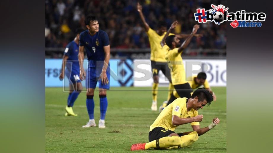 Irfan (kanan) meraikan kejayaan Malaysia selepas pemain Thailand, Adisak Kraisorn (kiri) gagal menjaringkan penalti. FOTO AFP