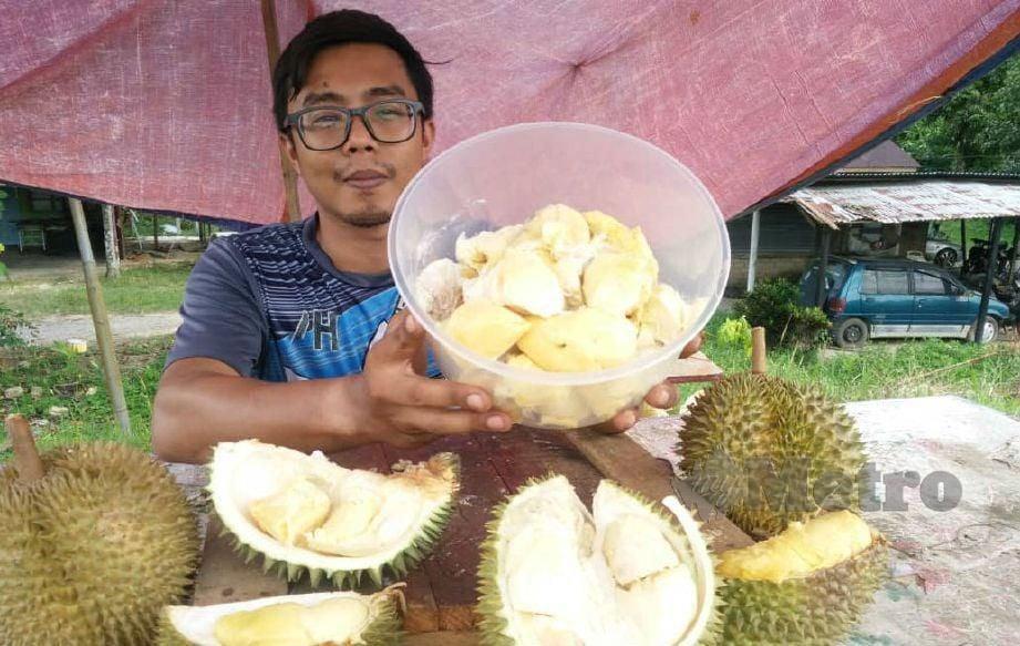 MOHD Izzuwan menunjukkan isi durian yang dijual digerainya. FOTO Noorazura Abdul Rahman