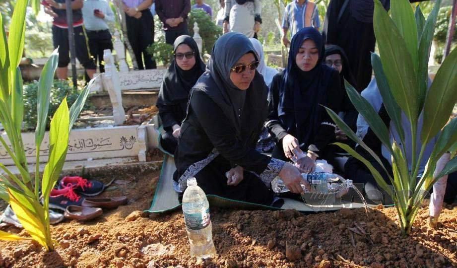 JAMILAH, isteri kepada Allahyarham Mohd Khusairi  menyiram air dipusara di Tanah Perkuburan Islam Felda Sungai Behrang. FOTO Sharul Hafiz Zam