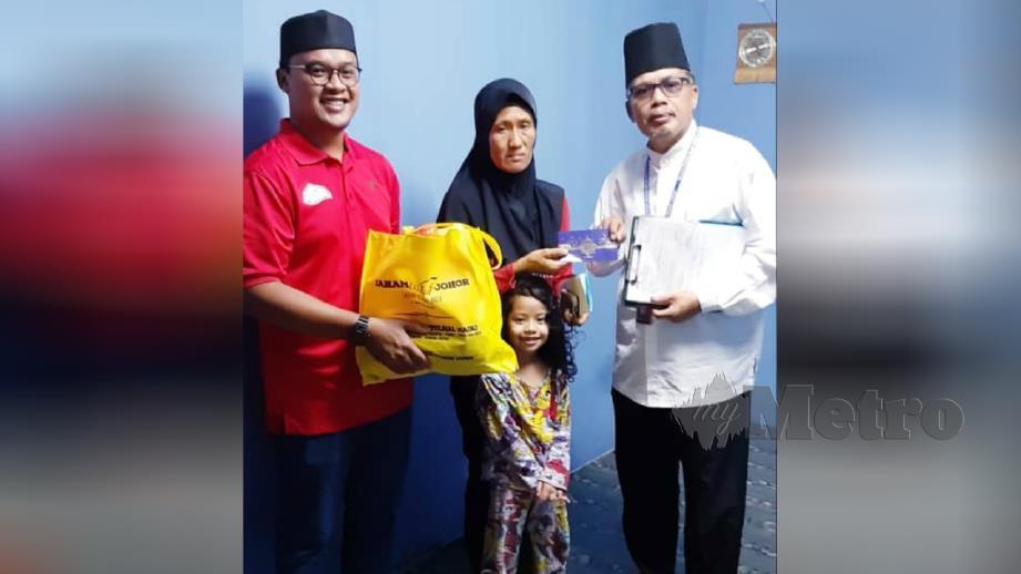 MOHD Nasir (kanan) menyampaikan sumbangan kepada Rosnani di Flet Taman Desa Tebrau, Johor Bahru, hari ini. FOTO ihsan MAIJ.