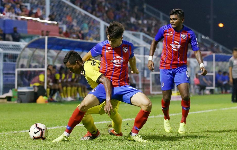 PEMAIN JDT II, Sean Gan Giannelli (tengah) diasak pemain PDRM, Muhamad  Eskandar Ismail (kiri) ketika perlawanan Liga Perdana 2019 di Stadium Majlis Perbandaran Pasir Gudang. FOTO Mohd Azren Jamaludin