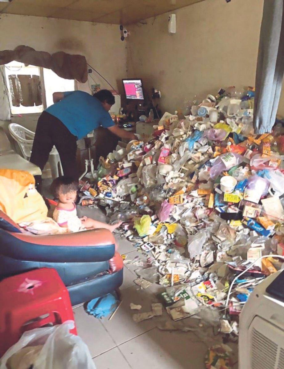 PEKERJA membersihkan timbunan sampah  dengan seorang daripada bayi berkenaan duduk di atas kerusi.