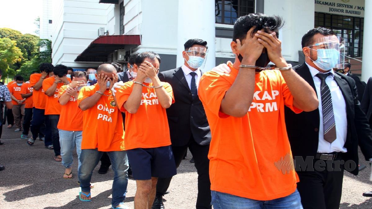 SEBAHAGIAN daripada 13 individu termasuk sembilan anggota JIM  keluar dari Mahkamah Majistret Johor Bahru. FOTO ZAIN AHMED