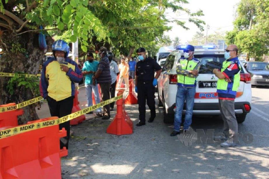 KETUA Polis Daerah Kubang Pasu, Superintendan Mohd Ismail Ibrahim (kanan) bersama pegawainya melihat pergerakan orang ramai di perkarangan masuk pasar awam di Kodiang. FOTO ZULIATY ZULKIFFLI