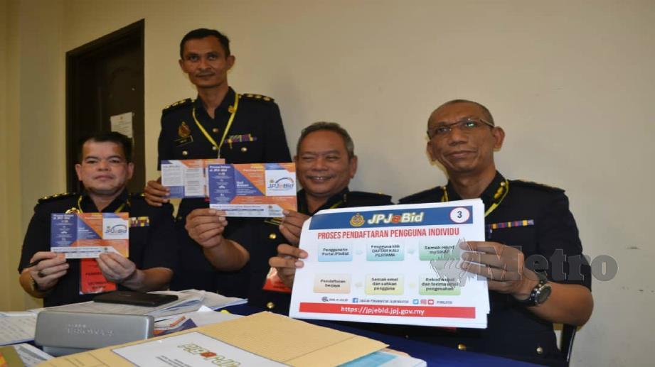 Mohammad (kanan) menunjukkan risalah berkaitan JPJeBid Pahang. Foto Asrol Awang