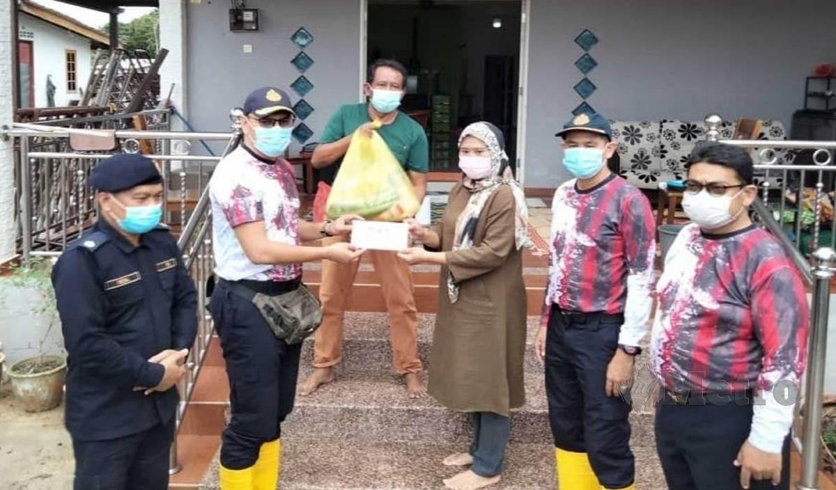 ZULKARNAIN (dua kiri) menyampaikan bantuan kepada  anggota dan kakitangan yang ditenggelami banjir di Kampung Gong Pauh. FOTO ZAID SALIM