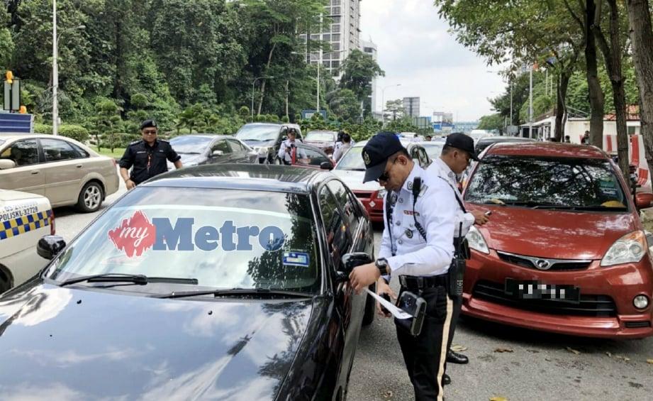 ANGGOTA dan pegawai JSPT Kuala Lumpur mengeluarkan saman kepada pemandu kenderaan yang membuat halangan dalam Ops Halangan di beberapa jalan utama di ibu kota, semalam. FOTO Hafidzul Hilmi Mohd Noor.