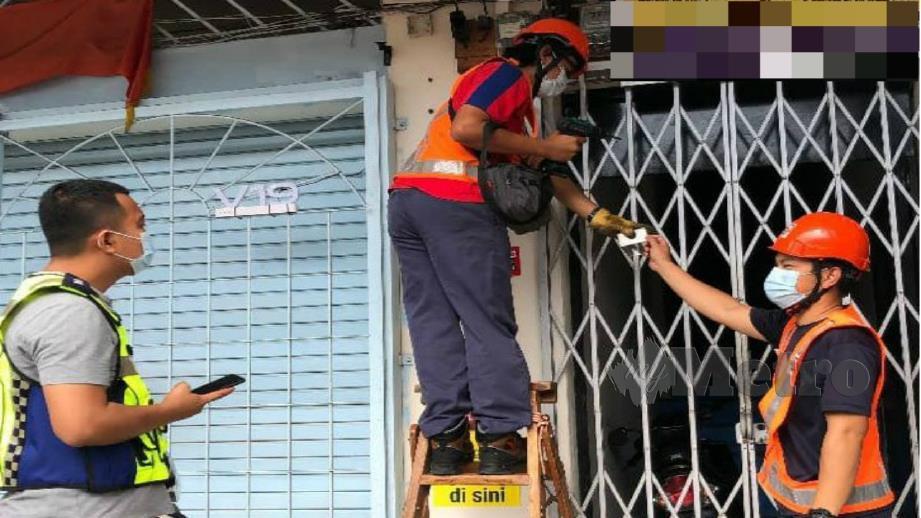 Anggota polis memerhatikan kerja memotong bekalan elektrik yang dilakukan oleh kakitangan TNB terhadap premis yang terbabit dalam aktiviti perjudian di Kluang. Foto Ihsan PDRM