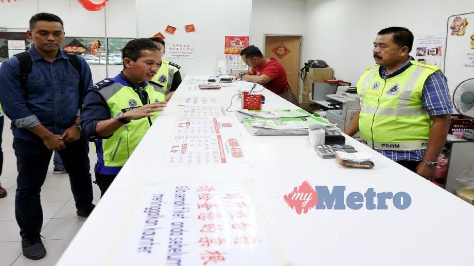 ROHAIMI (dua kiri) memeriksa barangan yang dirampas di pusat judi loteri haram. FOTO Mikail Ong