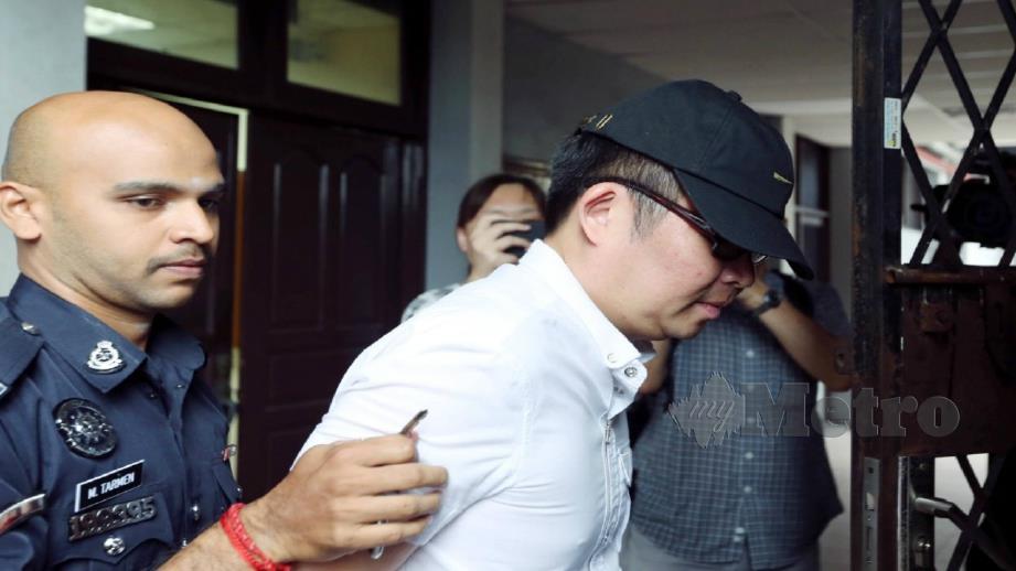 U Gene diiringi anggota polis selepas dituduh di Mahkamah Majistret Ipoh hari ini atas dakwaan menipu seorang usahawan. Foto Muhaizan Yahya