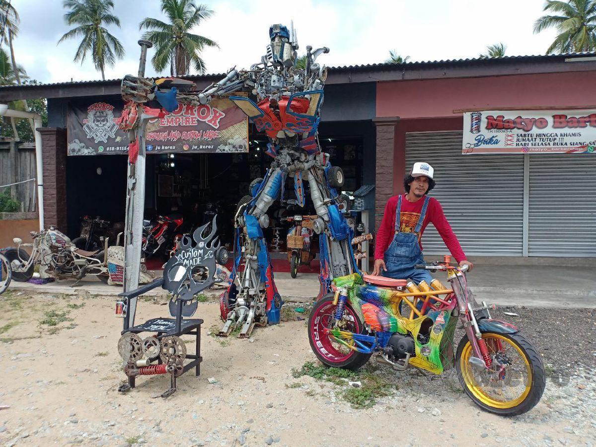 RAJA Junaidi dari Kampung Rhu Muda bersama motosikal custom dan replika Transformers yang dibinanya di hadapan bengkel custom motosikal miliknya. FOTO AHMAD RABIUL ZULKIFLI