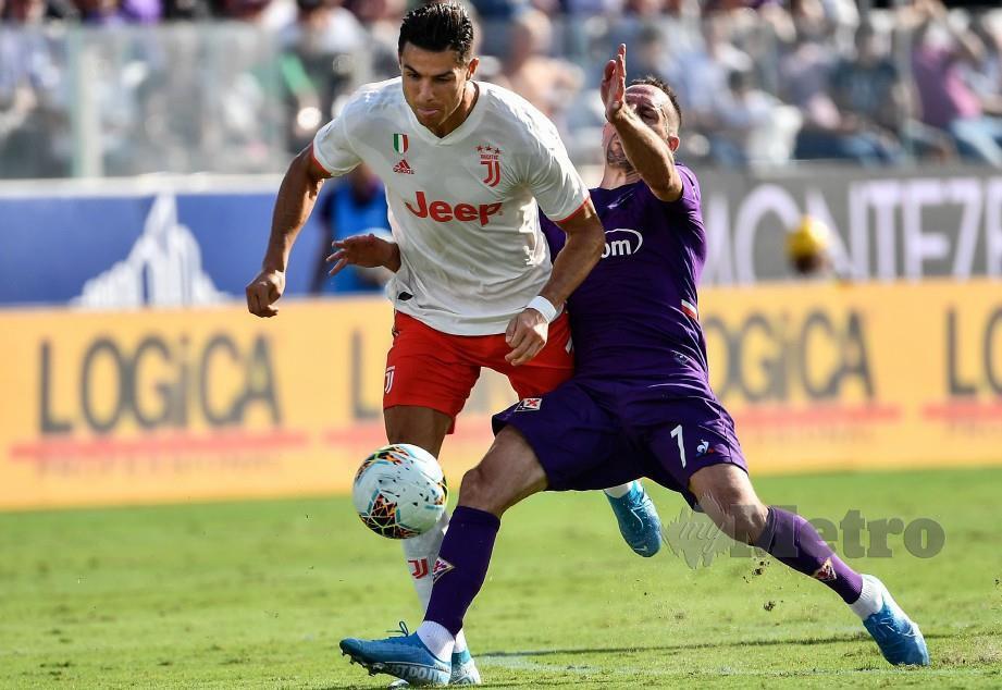 RONALDO (kiri) dibentes pemain Fiorentina, Franck Ribery pada aksi di Stadium Artemio-Franchi, Florence. — AFP