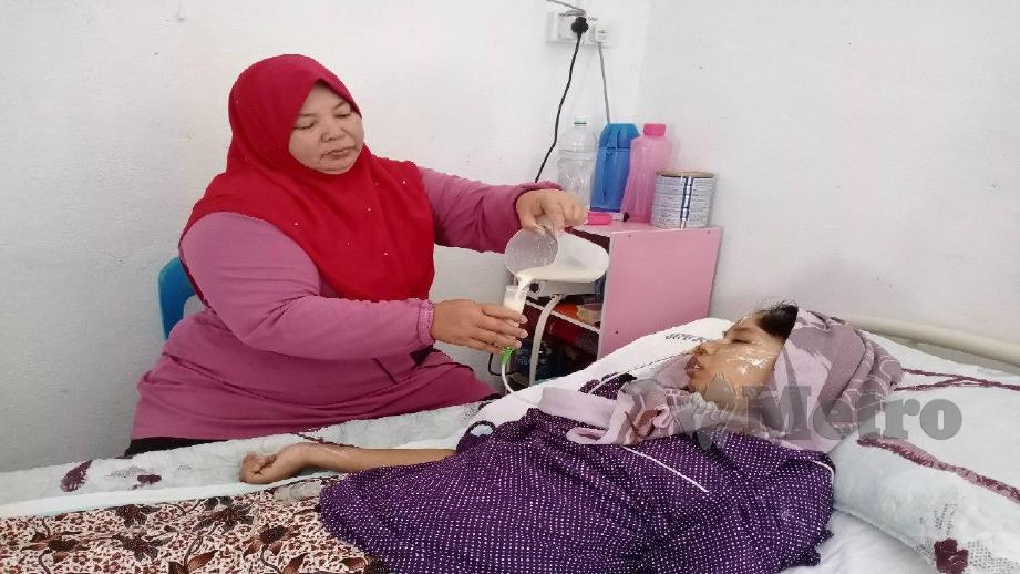 LATIFAH memberi Nur Atiqah susu melalui tiub khas di bahagian leher selepas terlantar sakit akibat strok sejak April lalu. Foto Noorazura Abdul Rahman