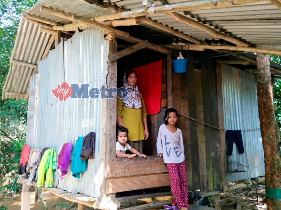 RUSLIDA dan dua anaknya di kandang kambing yang dijadikan rumah sejak setahun lalu.  FOTO Ramli Ibrahim