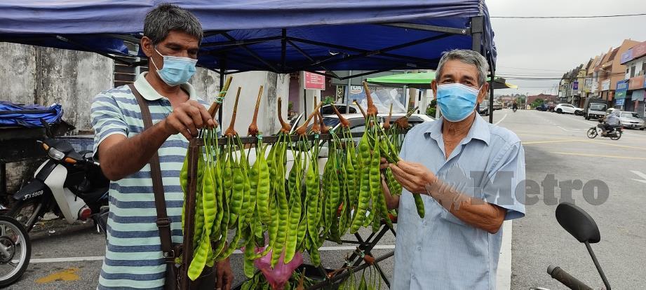 MOHD Kamaruzaman (kiri) menjual petai padi kepada pelanggan di pekan Slim River. FOTO Rosman Shamsudin
