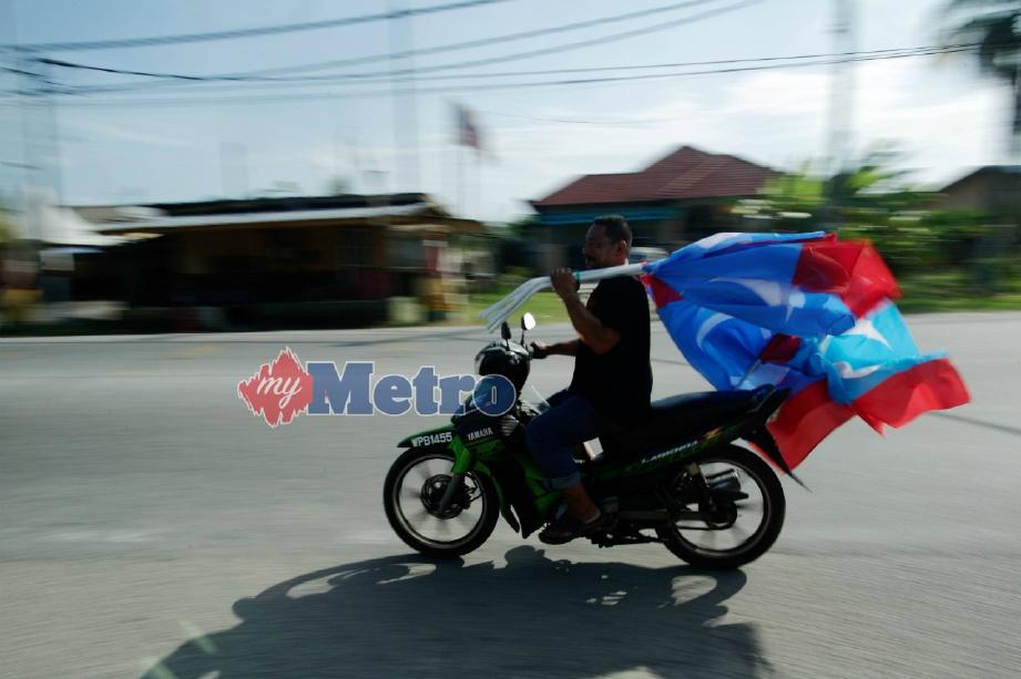 PETUGAS PKR, Ujang Johari  membawa bendera parti untuk dipasang sempena PRK DUN Sungai Kandis. FOTO Syarafiq Abd Samad