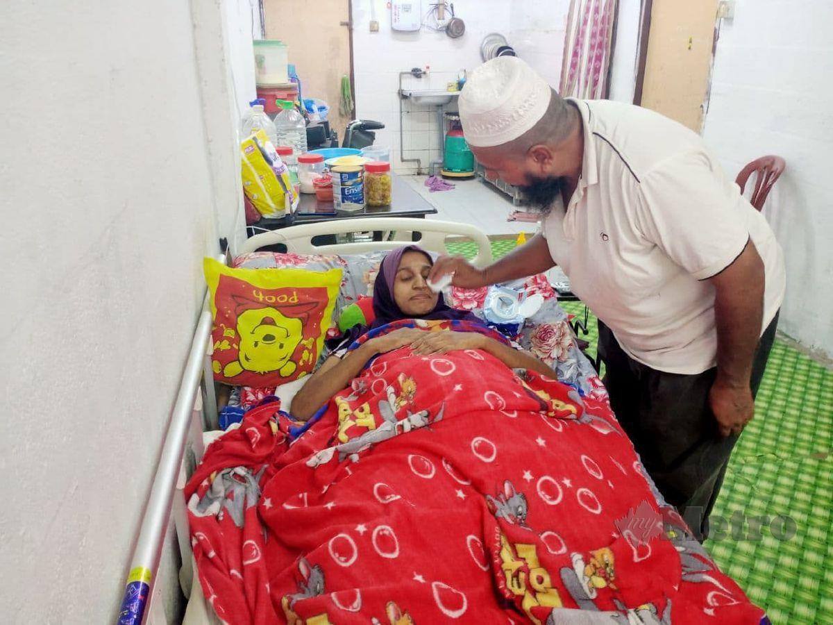 RASILA sedang diuruskan suaminya ketika ditemui di rumahnya di Flat Taman Andalas, Mantin, Seremban. FOTO MOHD KHIDIR ZAKARIA