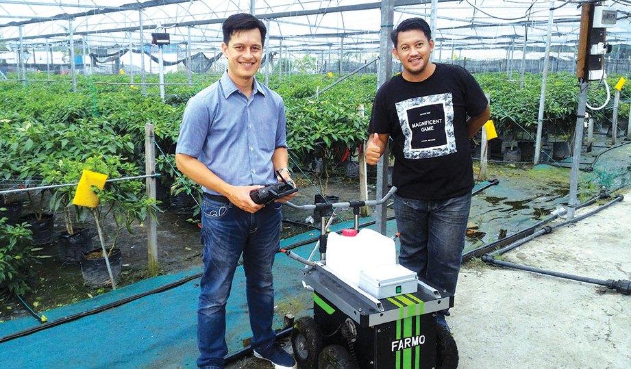MOHD Ashraf bersama pemilik kebun cili, Ikmal semasa pengujian robot di Kebun Pewaris Bumi Hijau, Kuala Langat.