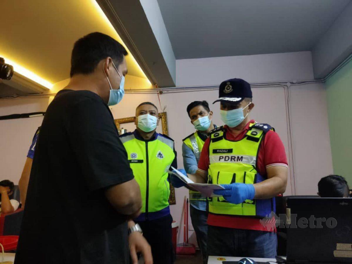RAZALI (kanan) menjalankan pemeriksaan di sebuah premis judi di Seri Kembangan. FOTO ihsan polis