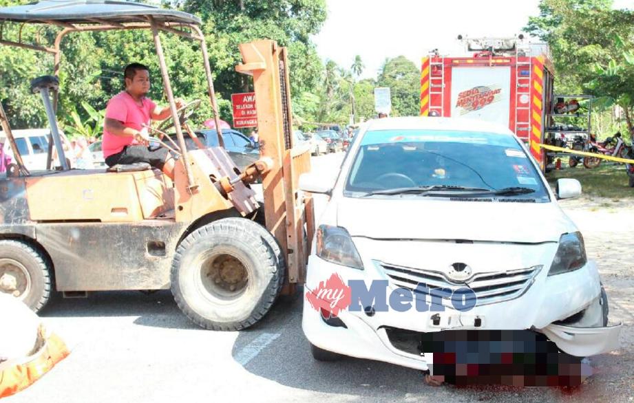 FORKLIFT digunakan untuk mengangkat kereta dan mengeluarkan mangsa yang digilis selepas tercampak dari motosikal dalam kemalangan di Jalan Pasir Mas-Tanah Merah dekat Kampung Kangkung, Pasir Mas, hari ini. FOTO Nik Abdullah Nik Omar