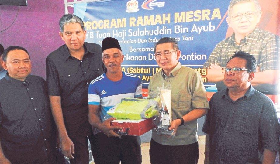 SEORANG nelayan menerima bantuan 'touch point' daripada Salahuddin (kanan).