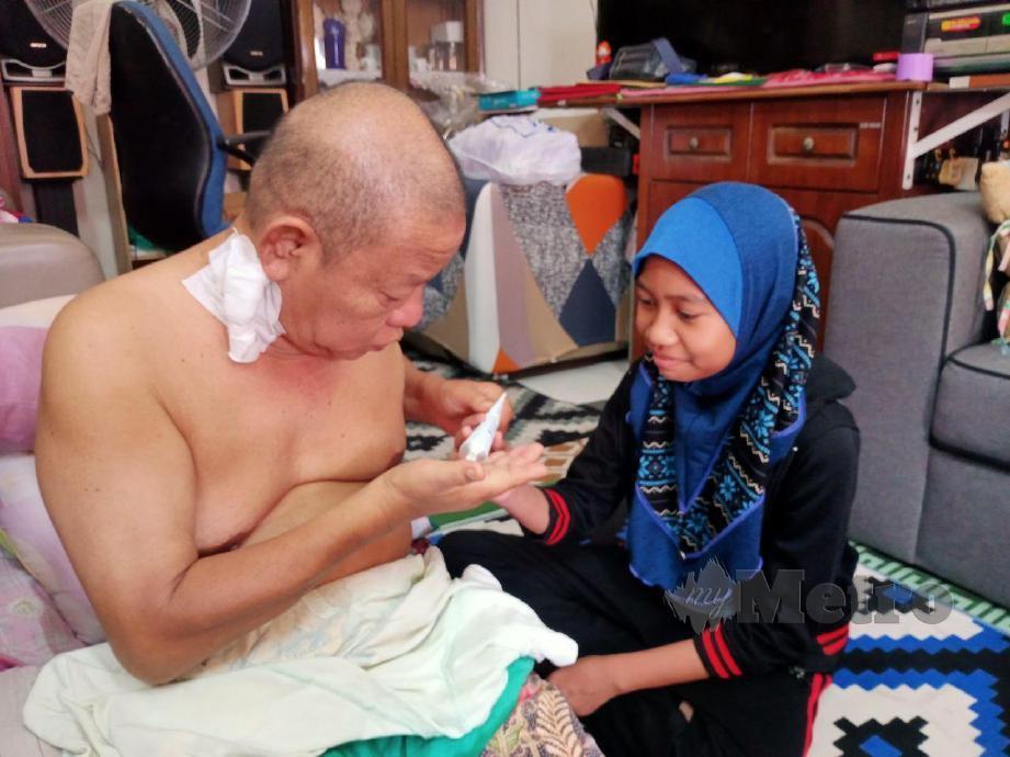 NUR KASIH (kanan) memberi ayah ubat ketika ditemui di rumahnya di Taman Rasah Jaya, Rasah. FOTO MOHD KHIDIR ZAKARIA